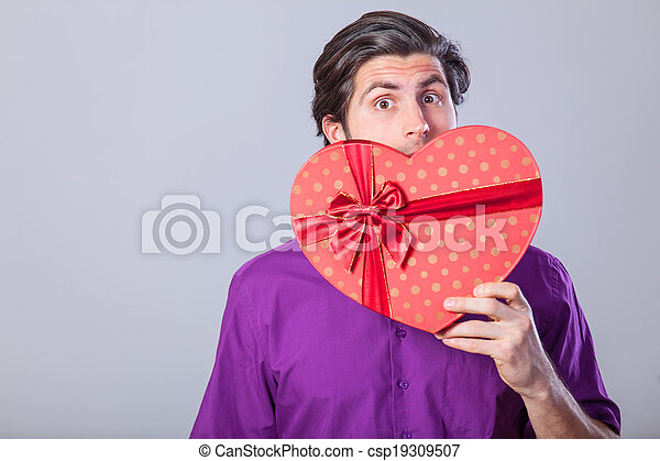 Handsome man with gift on gray background. - csp19309507