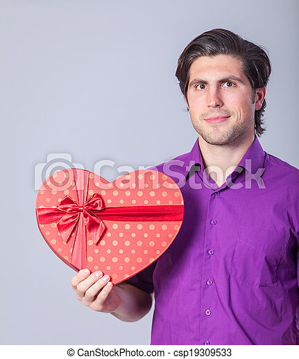 Handsome man with gift on gray background. - csp19309533