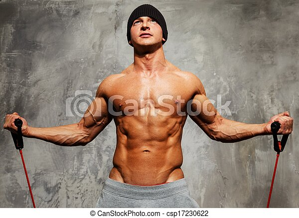 Handsome man with muscular body doing fitness exercise .