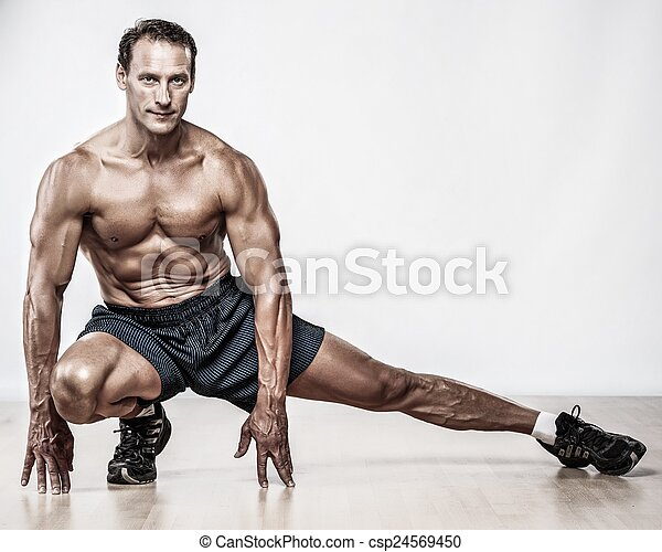 Handsome muscular man doing stretching exercise - csp24569450