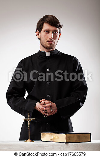 Handsome reverend with crucifix and the Bible - csp17665579