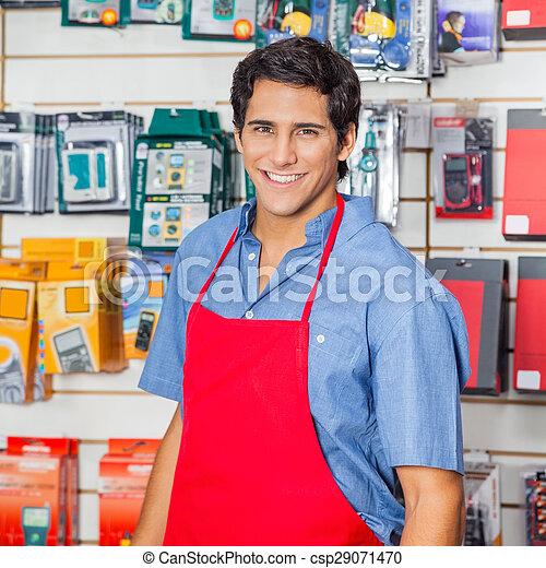 Handsome Salesman In Red Apron Smiling At Hardware Shop - csp29071470
