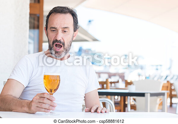 Handsome senior man drinking beer at restaurant scared in shock with a  surprise face, afraid and excited with fear expression