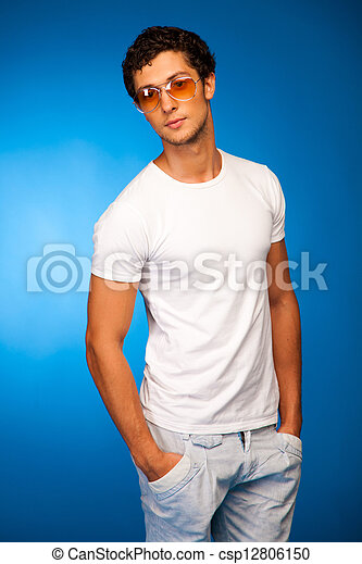handsome sexy boy over blue background in studio - csp12806150