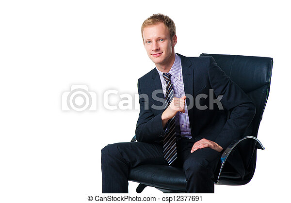 handsome smiling businessman sitting in black office chair - csp12377691