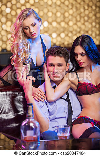 Handsome successful business man having fun in strip club. Beautiful dancers hugging man from both sides  - csp20047404