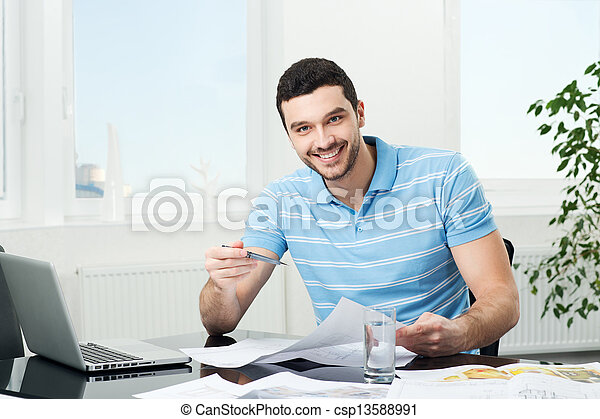 handsome young interior designer at workplace - csp13588991