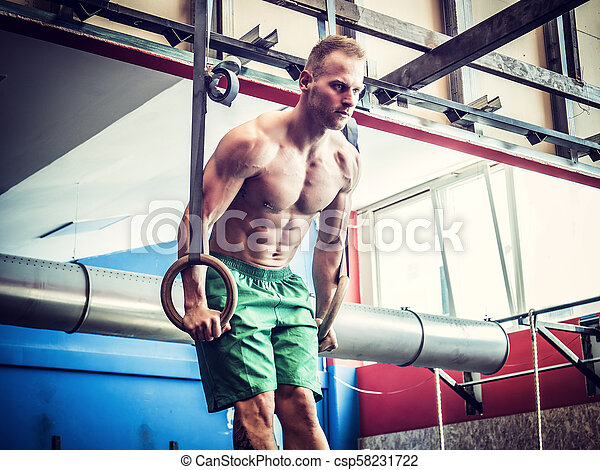 Handsome young man exercising with rings - csp58231722
