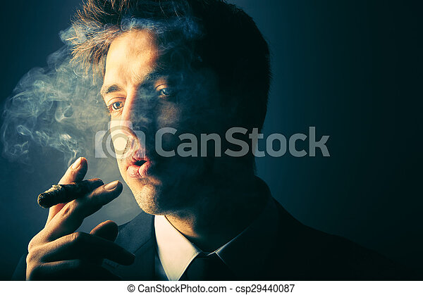 Handsome young man smoking cigar - csp29440087