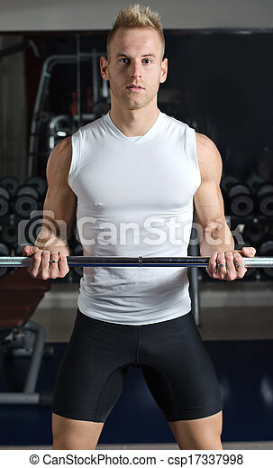Handsome young man training biceps lifting barbell - csp17337998