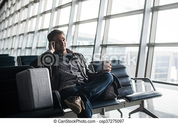 handsome young man with black hair working, sitting on a chair things at the airport waiting for his flight - csp37275097