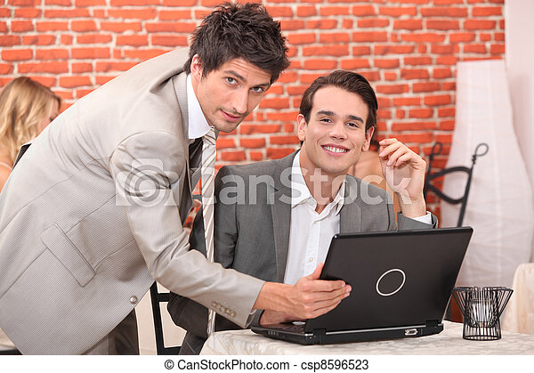 Handsome young men working at a laptop - csp8596523