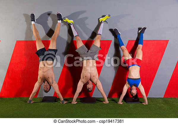 Handstand push-up group workout at gym - csp19417381
