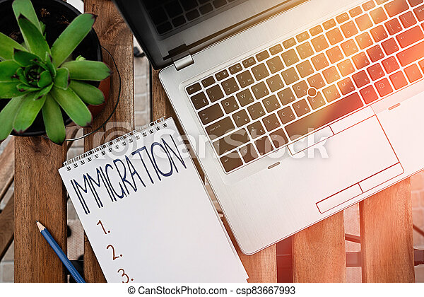 Handwriting text Immigration. Concept meaning the action of coming to live permanently in a foreign country Personal workplace overview with laptop device used for individual interest. - csp83667993