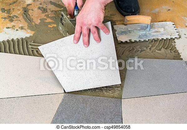 Handyman Laying Ceramic Floor Tiles On Adhesive Using Trowel