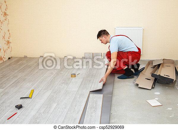 Handyman Laying Down Laminate Flooring Boards While Renovating A House
