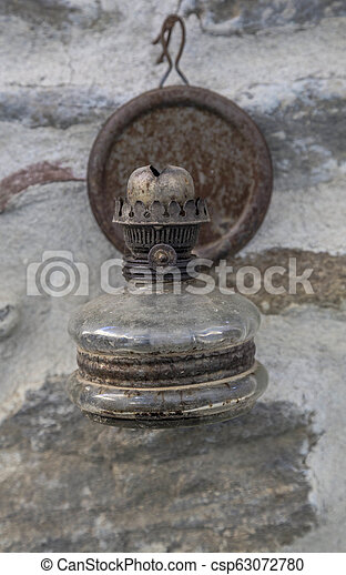 hanged old oil lamp on wall - csp63072780