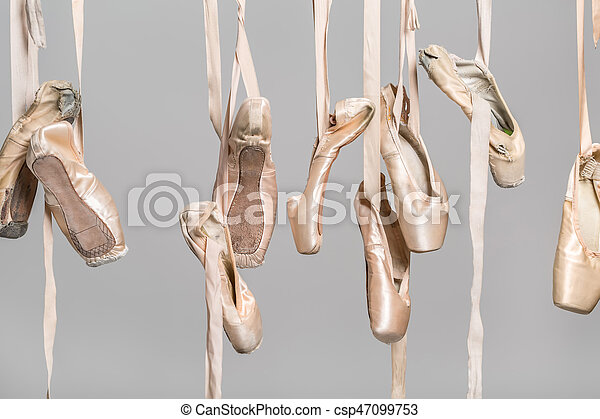 15ed0cc62dfd Hanging ballet shoes. Several hanging beige ballet shoes on the gray ...