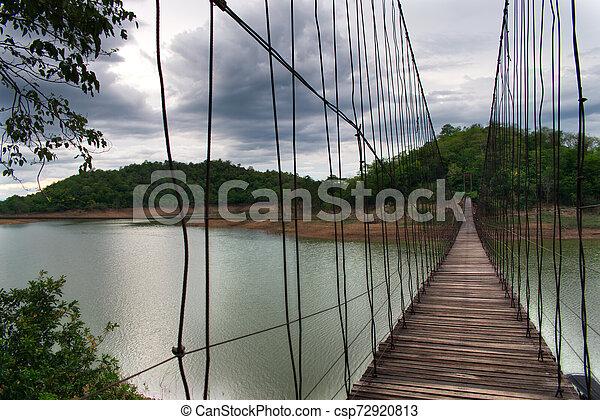 Hanging Bridge over the reservoir at sunset, Kang Krajarn National Park - csp72920813
