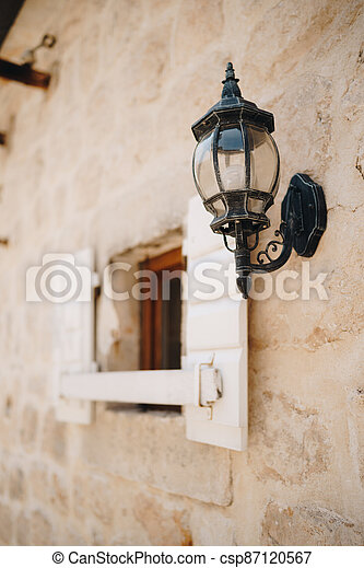 Hanging street lamp in black on the wall by a window with open shutters. - csp87120567