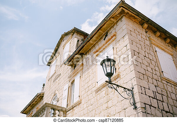 Hanging street lamp on the wall of the building near the balcony and roof windows. - csp87120885