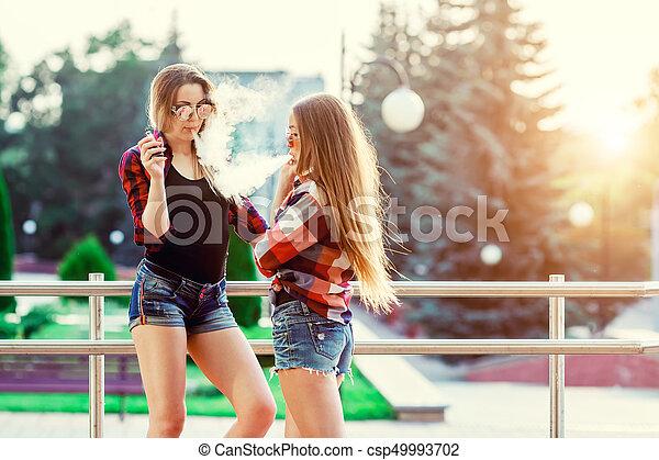 hanglejtés, este, city., image., outdoor., két, napnyugta, vaping, felett, nők - csp49993702