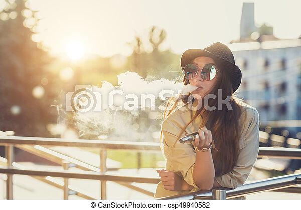 hanglejtés, nő, image., ecig, vape, fiatal, csípőre szabott, fekete, meglehetősen, eszköz, vaping, kalap, sunset. - csp49940582