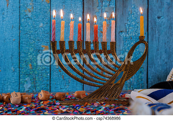 Hanukkah celebration with menorah with wooden dreidels and candles - csp74368986