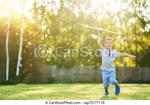 Happy 3 year old boy having fun playing with big plane outdoors - csp72177118