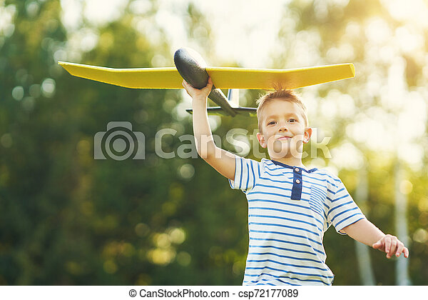 Happy 3 year old boy having fun playing with big plane outdoors - csp72177089