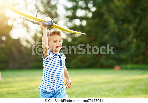 Happy 3 year old boy having fun playing with big plane outdoors - csp72177041
