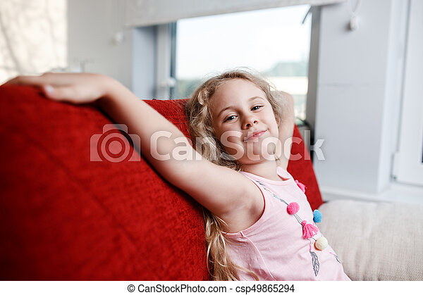 Happy 6 year old girl is sitting on red chair in his room. - csp49865294