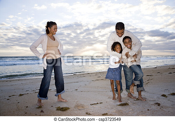 Happy African-American family of four on beach - csp3723549