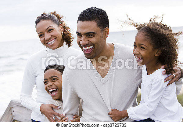 Happy African-American family of four on beach - csp3723733