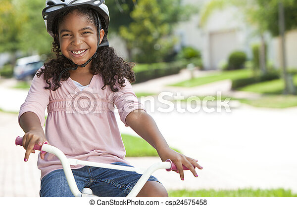 Happy African American Girl Riding Bike Smiling - csp24575458