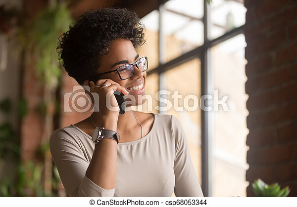 Happy african american young businesswoman talking on phone in office - csp68053344