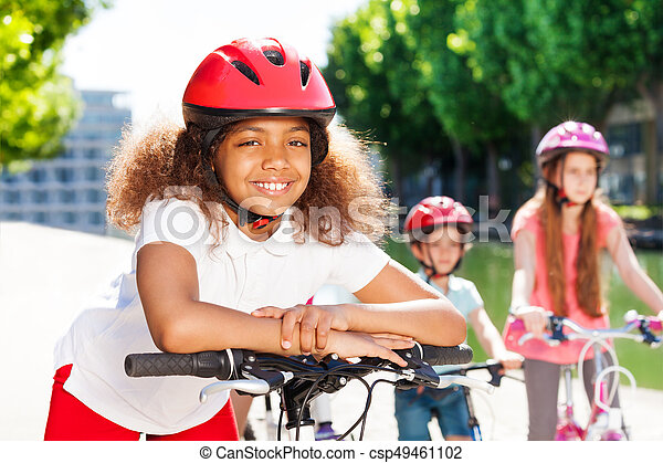 Happy African Girl Riding Bicycle In Summer City Portrait Of Happy African Girl In Safety Helmet Riding Her Bicycle In