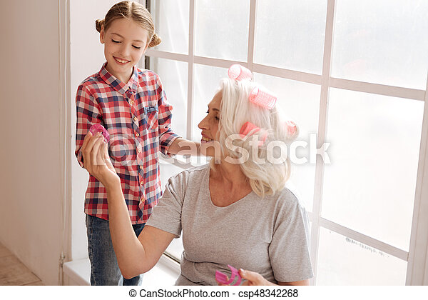 Take it. Happy nice aged woman smiling and looking at the hair roller while giving it to her granddaughter