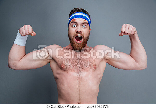 Happy amazed young sportsman standing and showing biceps - csp37032775