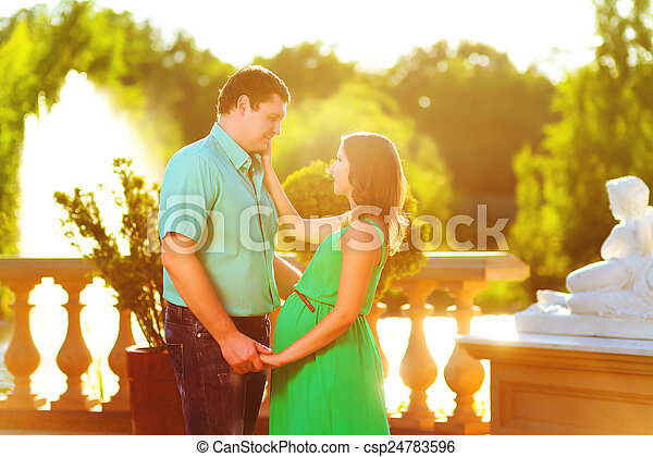 Happy and young pregnant couple hugging in nature - csp24783596
