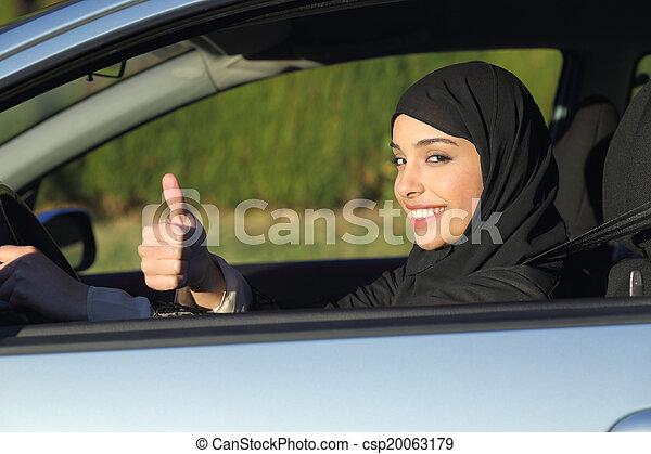 Happy arab saudi woman driving a car with thumb up - csp20063179
