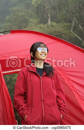 Happy asian girl with red tent outdoors - csp5965470 & Happy asian girl with red tent outdoors. Happy asian girl wearing ...
