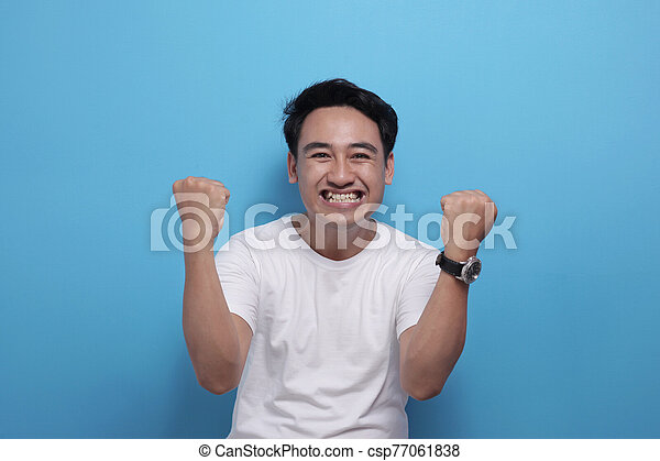 Happy Asian man shows winning gesture, celebrating victory - csp77061838