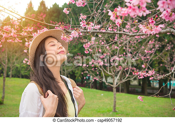 Happy Asian Woman Enjoying Smell Pink Flowers