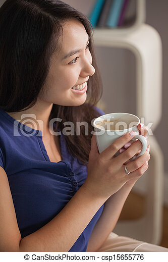 Happy asian woman sitting on the couch holding mug of coffee looking away in sitting room at home - csp15655776