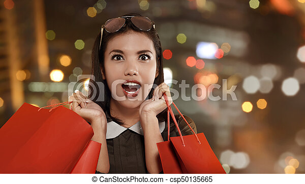 Happy asian woman with red shopping bag celebrating Black Friday on the mall