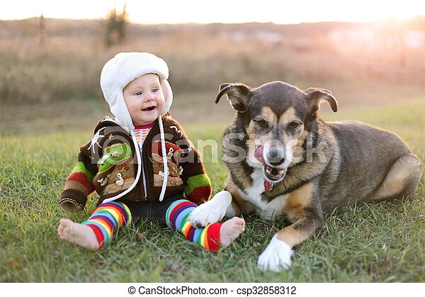 Happy Baby Bundled up Outside in Winter with Pet Dog - csp32858312