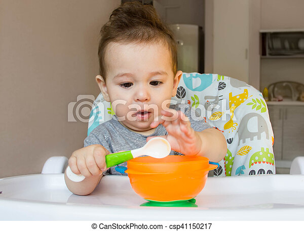 happy baby child sitting in chair with a spoon - csp41150217