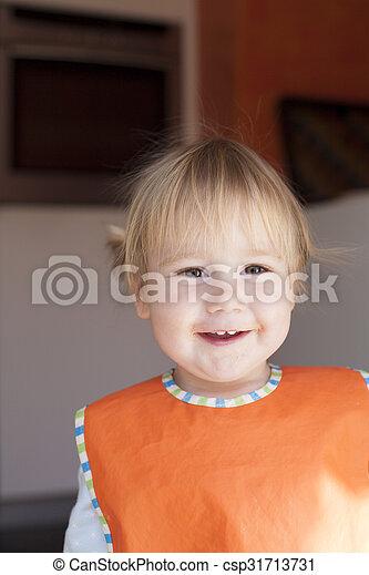 happy baby face orange bib looking - csp31713731