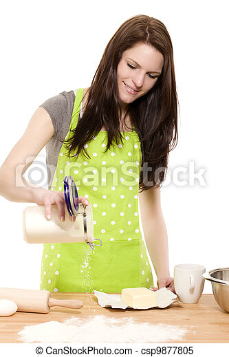 happy baking woman pouring flour on a table with white background - csp9877805
